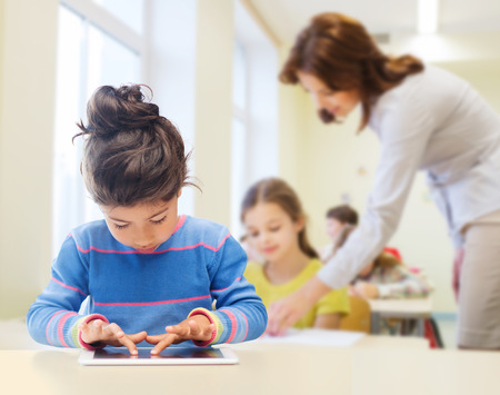 Foto de education, elementary school, technology and children concept - little student girl with tablet pc over classroom and teacher background - Imagen libre de derechos