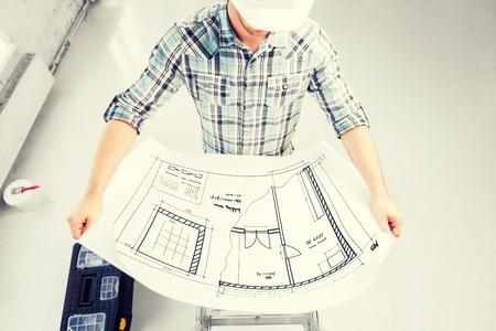 Photo pour male architect in helmet with blueprint - image libre de droit