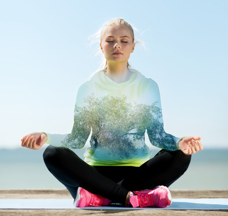happy young woman meditating in lotus pose over blue sky with sea and tree background