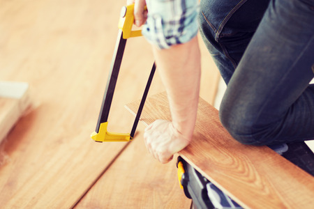 close up of male hands cutting parquet floor board with saw