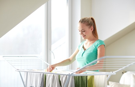 people, housework, laundry and housekeeping concept - happy woman hanging clothes on dryer at home