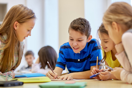 Photo for group of school kids with pens and papers writing in classroom - Royalty Free Image