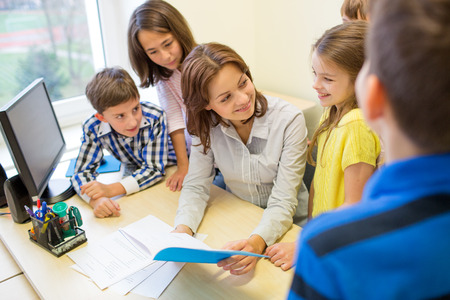 group of school kids with teacher talking in classroom