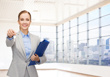 business, real estate, banking and people concept - smiling businesswoman with folder and keys over office room or new apartment background