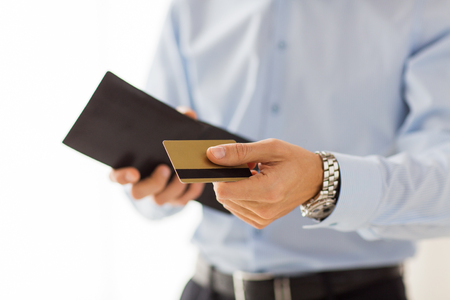 people, business, finances and money concept - close up of businessman hands holding open holding wallet and credit card