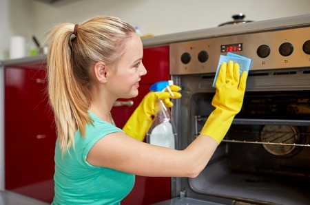 happy woman with bottle of spray cleanser cleaning oven at home kitchen