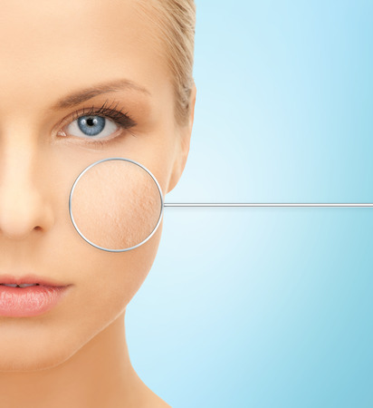 people, skin care and beauty concept - close up of beautiful young woman half face over blue background