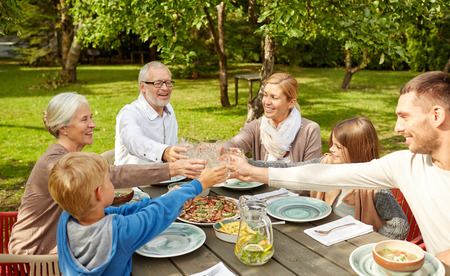 Foto de family, generation, home, holidays and people concept - happy family having dinner and clinking glasses in summer garden - Imagen libre de derechos