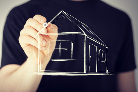 real estate, technology and accomodation - picture of man drawing a house on virtual screen