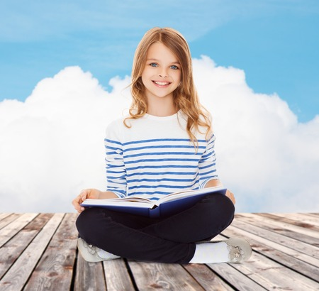 education, childhood, people and school concept - little student girl studying and reading book over blue sky and cloud background