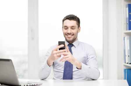 Photo pour business, office and technology concept - smiling businessman with laptop computer and smartphone at office - image libre de droit