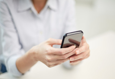 business, technology and people concept - close up of woman hands texting message on smartphone at officeの写真素材