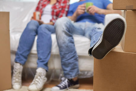 moving, home, repair and people concept - close up of couple legs relaxing and sitting on sofa with cups in new apartment