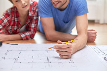 Foto de repair, building, renovation and people concept - close up of happy couple looking at blueprint at home - Imagen libre de derechos