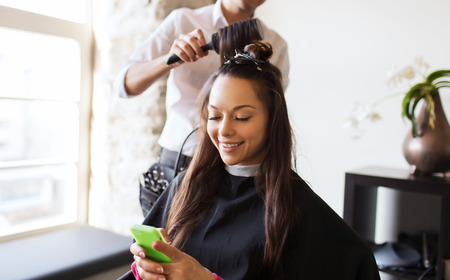 beauty, hairstyle and people concept - happy young woman with smartphone and hairdresser making hair styling at salon