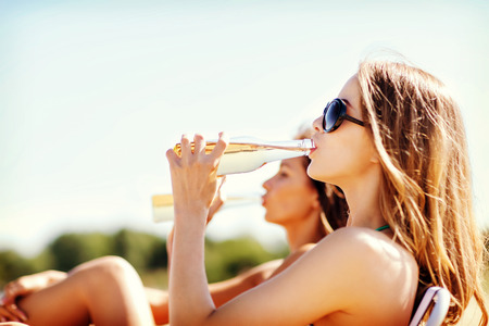 Foto de summer holidays and vacation - girls in bikinis with drinks on the beach chairs - Imagen libre de derechos