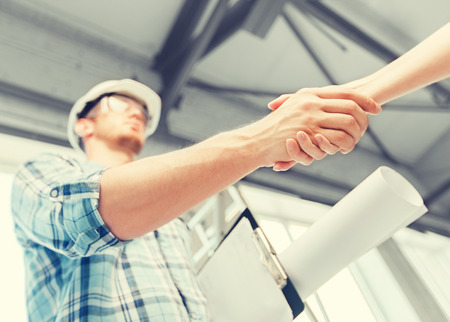 Photo for architecture and home renovation concept - builder with blueprint shaking partner hand - Royalty Free Image