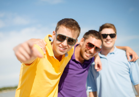 friendship, summer vacation, holidays and people concept - group of smiling male friends in sunglasses pointing at you on beach