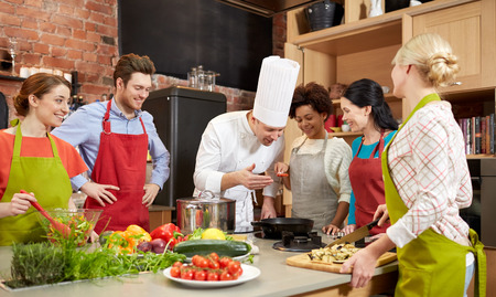 cooking class, culinary, food and people concept - happy group of friends and male chef cook cooking in kitchen