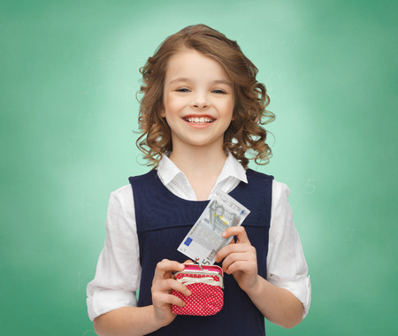 finances, childhood, school, people and education concept - happy little girl with purse and paper euro money over green chalk board background