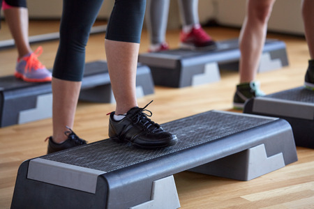 fitness, sport, people, step aerobics and lifestyle concept - close up of women legs exercising with steppers in gym