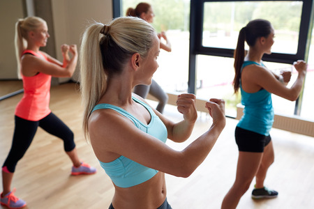 fitness, sport, training, people and lifestyle concept - group of women working out martial arts in gym