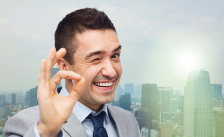 Foto de business, people, gesture and success concept - happy smiling businessman in suit showing ok hand sign over city background - Imagen libre de derechos