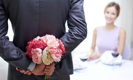 Photo pour restaurant, people, celebration and holiday concept - close up of man hiding flowers behind from woman at restaurant - image libre de droit