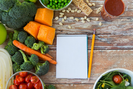 healthy eating vegetarian food advertisement and culinary concept  close up of ripe vegetables and notebook with pencil on wooden table