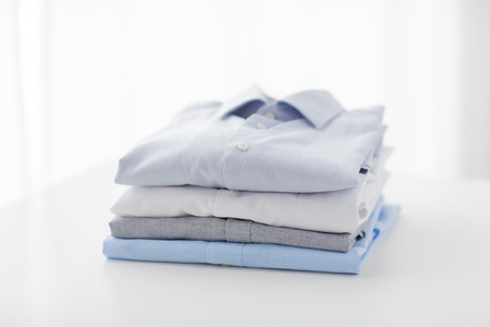 Photo pour ironing, laundry, clothes, housekeeping and objects concept - close up of ironed and folded shirts on table at home - image libre de droit