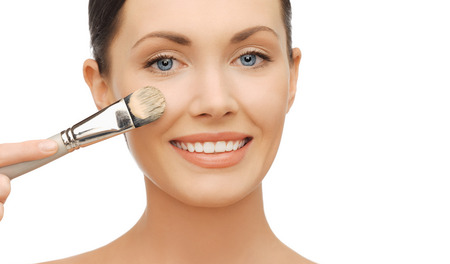 beauty and makeup concept - woman applying liquid foundation with brush