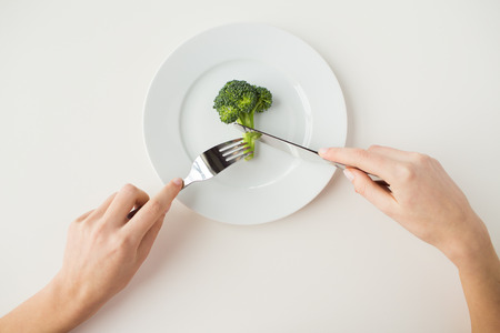 Photo pour healthy lifestyle, diet, vegetarian food and people concept - close up of woman with fork and knife eating broccoli - image libre de droit