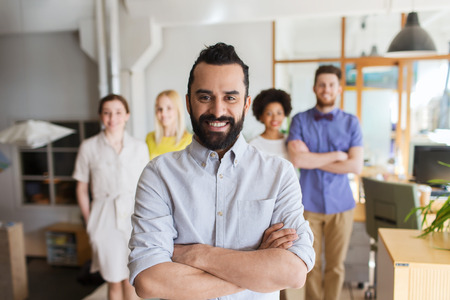Foto de business, startup, people and teamwork concept - happy young man with beard over creative team in office - Imagen libre de derechos