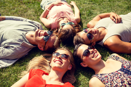 Photo pour friendship, leisure, summer and people concept - group of smiling friends lying on grass in circle outdoors - image libre de droit