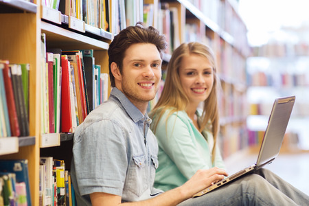 Photo for people, education, technology and school concept - happy students with laptop computer networking in library - Royalty Free Image