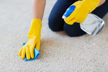 Photo pour people, housework and housekeeping concept - close up of woman in rubber gloves with cloth and detergent spray cleaning carpet at home - image libre de droit
