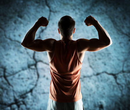 sport, fitness, bodybuilding, strength and people concept - young man or bodybuilder showing biceps over concrete wall background from backの写真素材