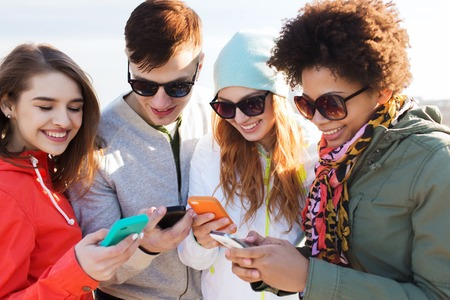 Photo pour people, friendship, cloud computing and technology concept - group of smiling teenage friends with smartphone outdoors - image libre de droit