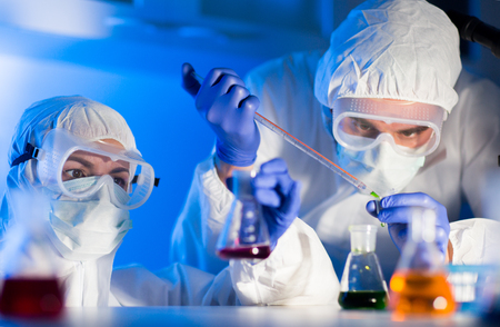 Photo for science, chemistry, biology, medicine and people concept - close up of young scientists with pipette and flasks making test or research in clinical laboratory - Royalty Free Image