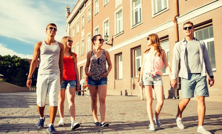 group of smiling teenagers walking in the city
