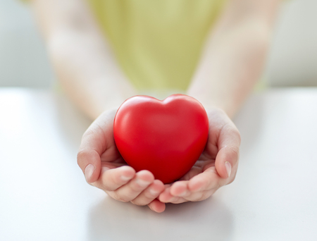 people, love, charity and family concept - close up of child hands holding red heart shape at home