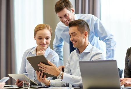 Foto de business, people and technology concept - smiling business team with tablet pc computer meeting in office - Imagen libre de derechos