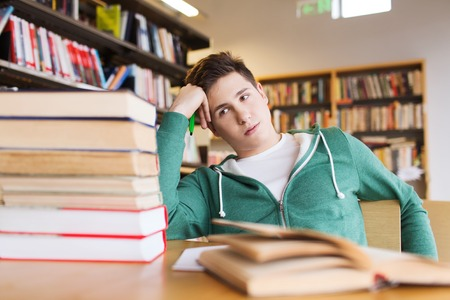 Foto de people, knowledge, education, literature and school concept - bored student or young man with books dreaming in library - Imagen libre de derechos