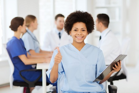 Foto de clinic, profession, people and medicine concept - happy female doctor or nurse with clipboard over group of medics meeting at hospital showing thumbs up gesture - Imagen libre de derechos