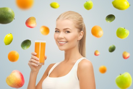 healthy eating, diet, detox and people concept - happy young woman holding glass of orange juice over gray background with falling fruits