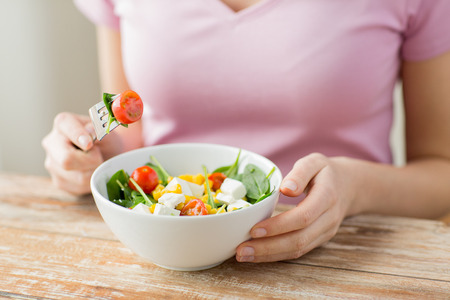 healthy eating, dieting and people concept - close up of young woman eating vegetable salad at home