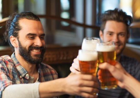 Photo for people, men, leisure, friendship and celebration concept - happy male friends drinking beer and clinking glasses at bar or pub - Royalty Free Image