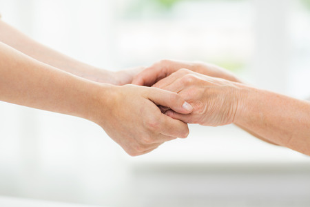 Photo pour people, age, family, care and support concept - close up of senior woman and young woman holding hands - image libre de droit