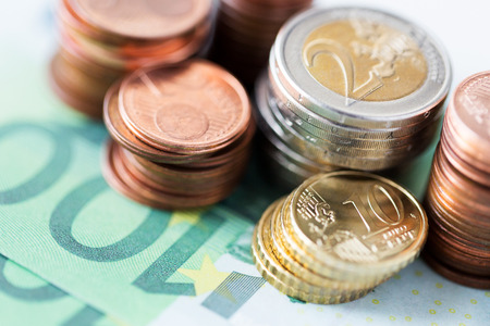 business, finance, investment, saving and cash concept - close up of euro paper money and coins on table