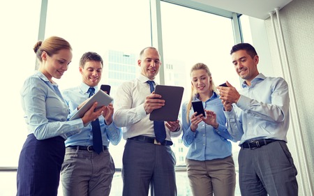 Photo pour business, teamwork, people and technology concept - business team with tablet pc and smartphones meeting in office - image libre de droit